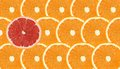 One grapefruit slice stand out of orange fruits Royalty Free Stock Photo