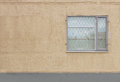 one gray window with a safety guard on the first floor of  modern building   beige background Plastered walls Royalty Free Stock Photo