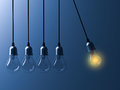 One hanging light bulb glowing different and stand out from unlit incandescent bulbs like newtons cradle on dark blue background