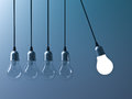 One hanging light bulb glowing different and stand out from unlit incandescent bulbs like newtons cradle on dark cyan Royalty Free Stock Photo