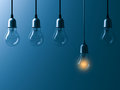 One hanging light bulb glowing different and standing out from unlit incandescent bulbs with reflection on dark cyan background Royalty Free Stock Photo