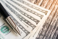One hundred dollar bills and pen on the wooden. Royalty Free Stock Photo