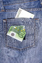 One hundred euro note in the back pocket of jeans full of holes concept poverty wastefulness Stock Image
