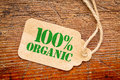 One hundred percent organic sign on a price tag paper against rustic red painted barn wood shopping concept Stock Photography