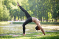 One legged upward bow pose profile of attractive sporty indian young man working out on riverbank in park doing bridge exercise Stock Image