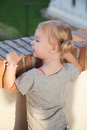 One little blonde girl looking out over stone brick wall Royalty Free Stock Photo