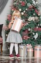 One little Caucasian cute girl smiling with present box in his hand in the festive New year studio room Royalty Free Stock Photo