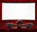 One man alone in empty cinema hall relaxed sitting with comfort like at home front of big screen Stock Images