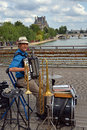 One man band entertainer on the pont des arts paris france july with accordion trumpet drum and trombone entertains tourists Royalty Free Stock Images