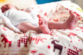 One month baby bare feet on Christmas sheet Royalty Free Stock Photo