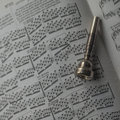 One old silver trumpet mouthpiece on sheet music book a Stock Photo