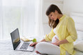 One pregnant european woman working from her home while she is sitting on a white bed at day time Royalty Free Stock Photo