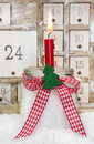 One red advent candle with a red checkered bow for christmas burning Royalty Free Stock Images