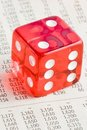 One red dice on the financial newspaper Royalty Free Stock Images