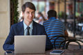 One relaxed young handsome professional businessman working with his laptop phone and tablet in a noisy cafe developed from raw Royalty Free Stock Photo