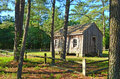 One room school house sitting on small piece of land surrounded by a wooden fence and pine trees Royalty Free Stock Photography