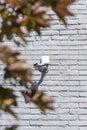 One security camera on grey brick wall