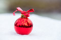 One shiny red christmas ball outside in snow Royalty Free Stock Photo
