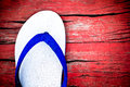 One side of white casual slippers on red wood background Royalty Free Stock Photo