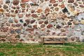 One small bench against the background of a stone wall Royalty Free Stock Photo