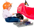 One small little girl wearing hard cap boots repairing toy red car isolated objects Royalty Free Stock Photography
