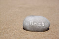 One stone pebbles with the word beach over sandy beach Royalty Free Stock Photo