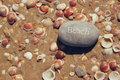One stone pebbles with the word beach  over sandy beach with shells Royalty Free Stock Photo