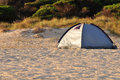 One tent on a sandy beach surrounded by vegetation Stock Photo