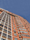 One urban high building, red brown brick, blue sky Stock Photos