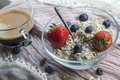 One usual glass bowl with old teaspoon, cereals, strawberries and blueberries, coffee Royalty Free Stock Photo