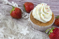 One vanilla cupcake with white cream and several strawberries Royalty Free Stock Photo