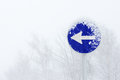 One way obligatory direction traffic sign with blizzard Royalty Free Stock Photo