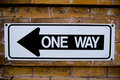 A one way sign against a brick wall Royalty Free Stock Photo
