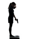 One woman standing on weight scale despair aiming gun silhouette studio on white background Royalty Free Stock Photo