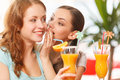 One woman whispering something to friend two girls sitting in cafe and drinking juice Stock Photos