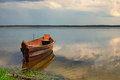 One wooden fishing boat on bank of the lake. Spring landscape photo. Volyn region. Ukraine Royalty Free Stock Photo