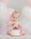 One year old birthday portraits with smash cake adorable little girl portrait white background tasting Royalty Free Stock Image