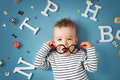 One year old child lying with spectacles and letters on blue background Royalty Free Stock Photo