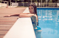 One young adult woman, posing, resting swimming pool edge, insid Royalty Free Stock Photo