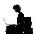 One young teenager girl silhouette computer computing laptop boo caucasian sitting books full length in studio cut out isolated on Royalty Free Stock Photo