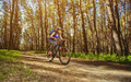 One young woman - cyclist in a helmet riding a mountain bike outside the city Royalty Free Stock Photo
