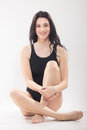 One young woman, sitting swimsuit, legs crossed Royalty Free Stock Photo