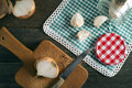 Onion and garlic glass jar on a checkered tablecloth onions knife Royalty Free Stock Image