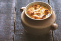 Onion soup in the ceramic pot on the wooden table horizontal Royalty Free Stock Photo