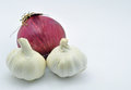 Onion and two garlic close up set against a light blue background shot Royalty Free Stock Photos