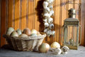 Onions and garlic on a basket braid hanging on wooden wall an oil lamp Stock Images