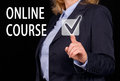 Online course text in white uppercase letters on a transparent touch screen with a businesswoman in black suit and gown pressing Stock Photos