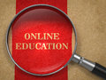 Online education magnifying glass concept on old paper with red vertical line background Stock Photo