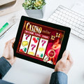 Online gambling concept with a businessman seated at his desk holding a tablet computer showing a casino interface with lucky Royalty Free Stock Photo