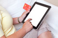 Online shopping a woman sat at home making an purchase on her tablet computer about to input her credit card details screen is Royalty Free Stock Photography